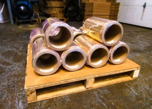 brass rolls stacked on wood pallet