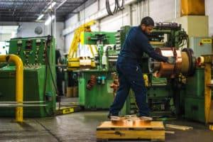 Vortex Metals employee processing copper rolls
