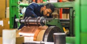 Vortex Metals employee setting up metal on machine