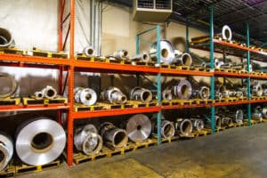 rolls of stainless steel on shelves at Vortex Metals