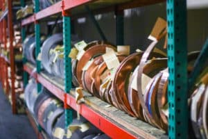 rolls of copper and metal on shelves at Vortex Metals